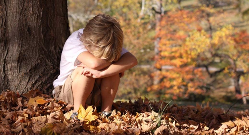 sad-child-sitting-by-tree